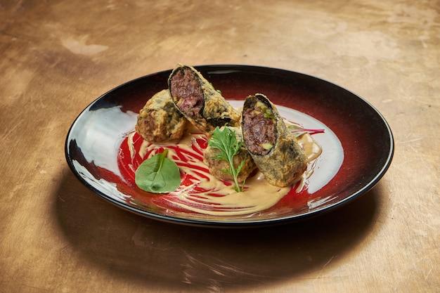 Surowy tatar wołowy z kaparami i pikantnym sosem w czerwonym talerzu ceramicznym.