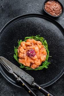 Surowy tatar z łososia lub tatar z czerwoną cebulą, rukolą i kaparami w czarnym talerzu
