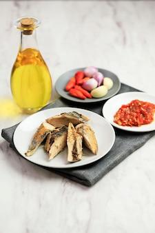 Surowy tuńczyk z makreli (pindang tongkol) na białym talerzu z olejem, pastą chili, czosnkiem i szalotką. podawać na białym tle marmuru z miejsca kopiowania. przygotowanie składników balado tongkol
