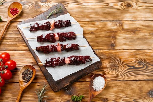 Surowy wątrobowy kebab na skewers na drewnianej desce