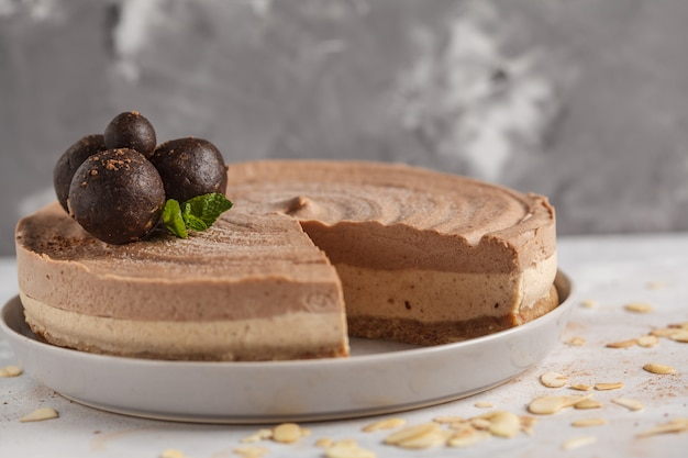 Surowy wegański sernik czekoladowo-karmelowy z surowymi słodkimi kulkami. koncepcja zdrowego wegańskiego jedzenia. jasnoszare tło.