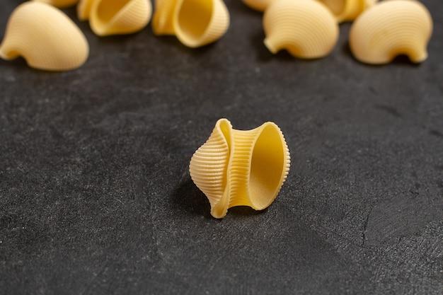 Surowy włoski makaron żółty kolor mało uformowany na ciemno