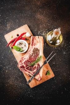 Surowy wołowy marmurkowaty mięso striplon stek z żeberka z przyprawami, ziołami