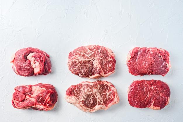 Surowy zestaw alternatywnych kawałków wołowiny chuck eye roll, górne ostrze, rumsztyk. mięso ekologiczne. białe tło z teksturą. widok z góry z miejscem na tekst.