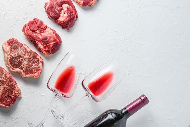 Surowy zestaw alternatywnych kawałków wołowiny chuck eye roll, górne ostrze, rumsztyk z czerwonym winem w kieliszku i butelce. mięso ekologiczne. białe tło z teksturą. widok z góry z miejscem na tekst.