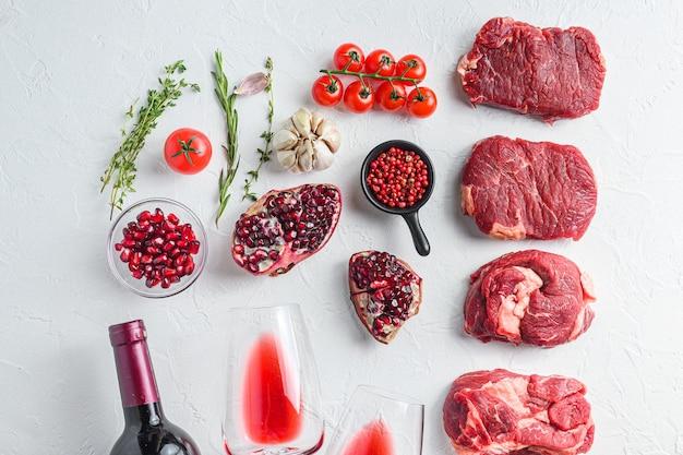 Surowy zestaw alternatywnych kawałków wołowiny chuck eye roll, górne ostrze, rumsztyk z czerwonym winem w kieliszku i butelce, ziołami i granatem. mięso ekologiczne. białe tło z teksturą. widok z góry.