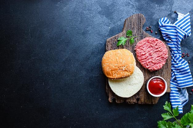 Surowy zestaw do burgerów kotlet, bułka, sos i nie tylko