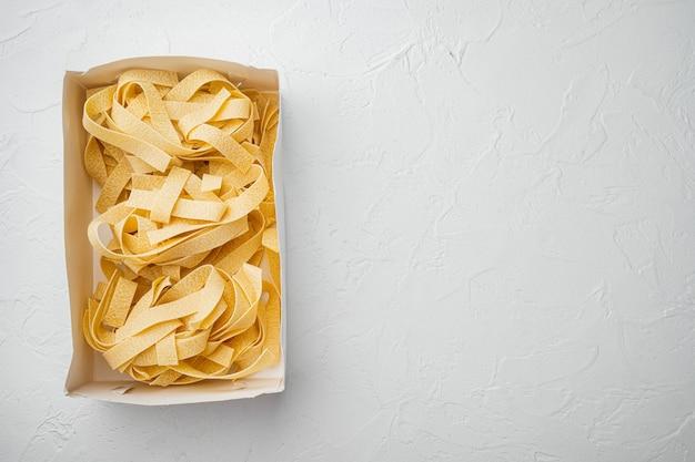 Surowy zestaw pappardelle, na białym tle kamiennego stołu, płaski widok z góry, z kopią miejsca na tekst