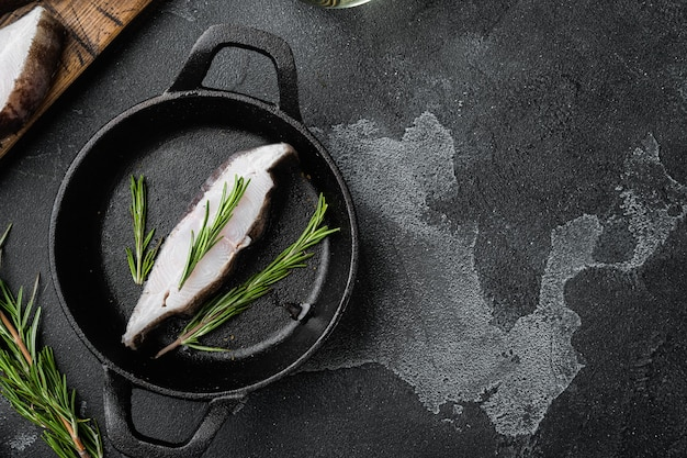 Surowy zestaw stek z ryby morskiej halibuta, ze składnikami i ziołami rozmarynowymi, na czarnym ciemnym tle kamiennego stołu, widok z góry płasko leżący, z miejscem na kopię na tekst