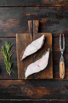 Surowy zestaw stek z ryby morskiej halibuta, ze składnikami i ziołami rozmarynowymi, na starym ciemnym tle drewnianego stołu, widok z góry płasko leżał