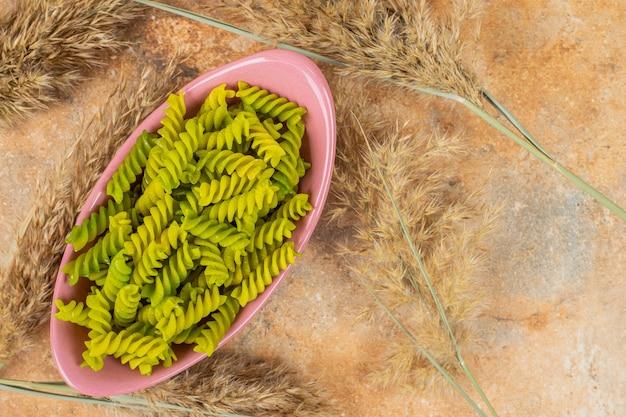 Surowy zielony makaron fusilli w misce obok trawy pampasowej, na marmurze.