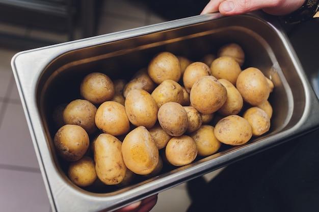 Surowy ziemniak w skórce w metalowej misce.