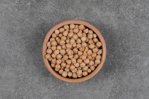 Surowy żółty groszek w drewnianej misce.