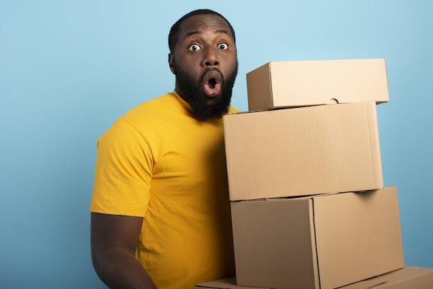 Surprised man posiada wiele otrzymanych paczek. niebieska ściana