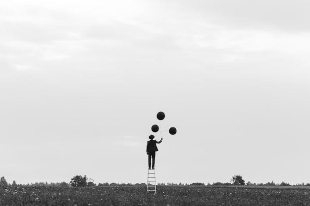 Surrealistyczna sylwetka mężczyzny w garniturze stojącego na schodach w polu z balonami. pojęcie wolności