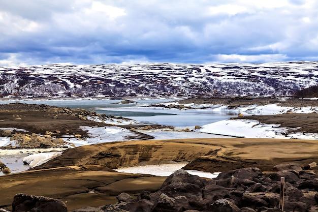 Surrealistyczny krajobraz: góry, jezioro i ziemia w skandynawii