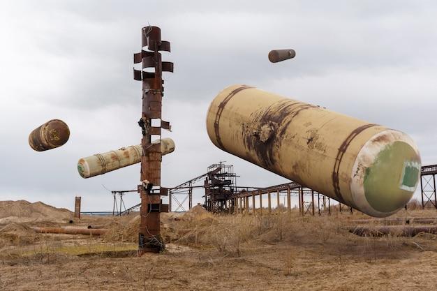 Surrealistyczny krajobraz ze starymi cysternami kolejowymi zawieszonymi w powietrzu nad nieużytkami przemysłowymi
