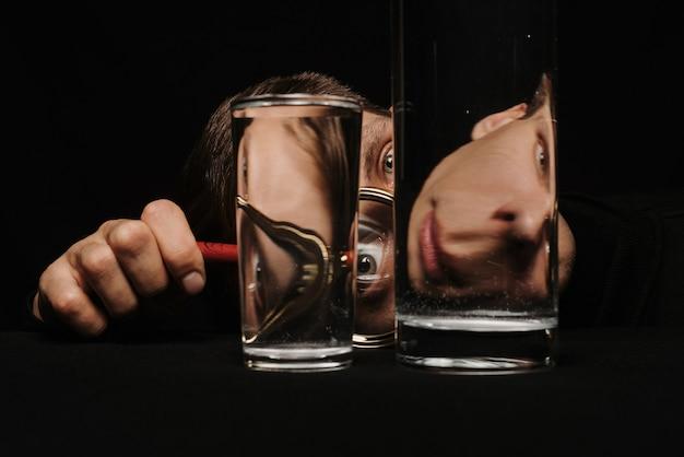 Surrealistyczny portret mężczyzny patrząc przez szkło powiększające i szklanki wody