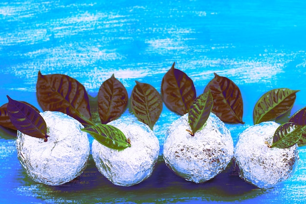 Surrealizm cztery jabłka owinięte w folię to naturalne zielone liście.