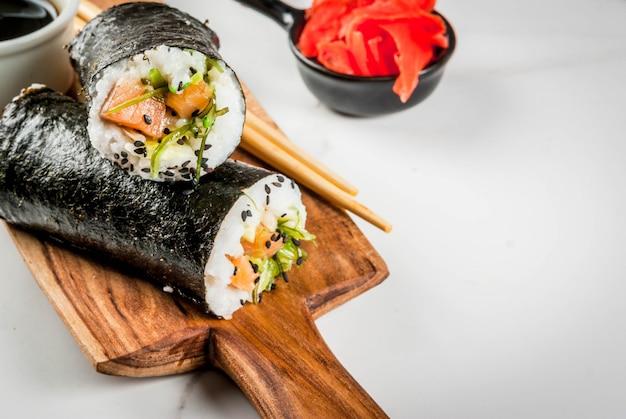Sushi-burrito, kanapka z łososiem, hayashi wakame, daikon, marynowany imbir, czerwony kawior.