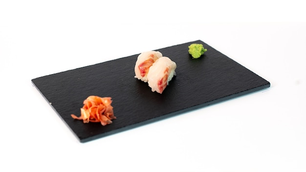 Sushi de pez mantequilla sobre tabla negra