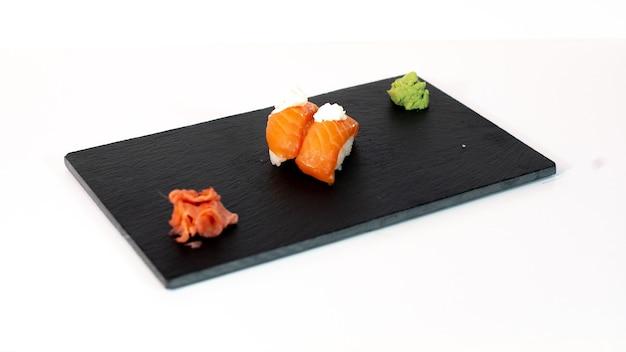 Sushi de salmón con queso sobre tabla negra