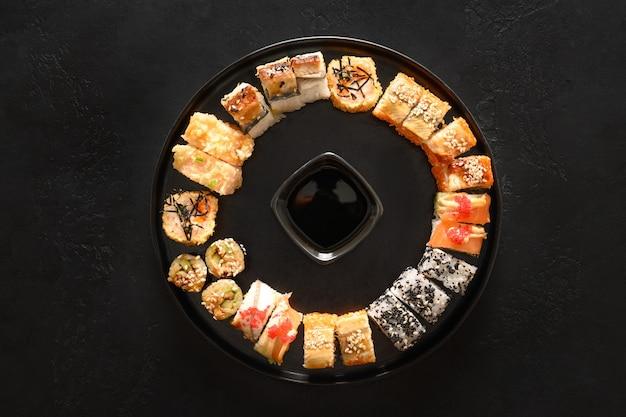 Sushi jako wieniec bożonarodzeniowy podawany z sosem sojowym na czarnym tle.
