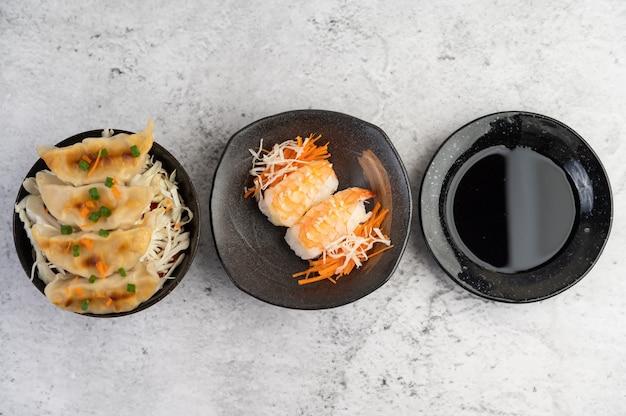 Sushi jest na talerzu z sosem zanurzeniowym na podłodze z białego cementu.