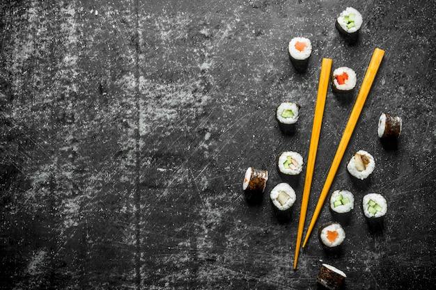 Sushi maki z pałeczkami na ciemnym stole rustykalnym