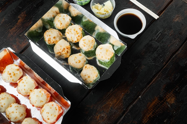 Sushi na wynos w pojemnikach, bułki philadelphia i zestaw pieczonych krewetek, na starym ciemnym drewnianym stole