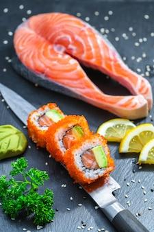 Sushi podawane na japońskim nożu na czarnym talerzu z łupków