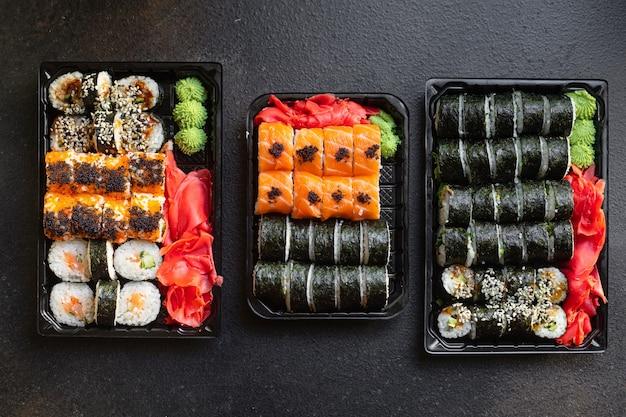 Sushi roladki rybne z łososiem, imbirowym ryżem wasabi i nori na stole