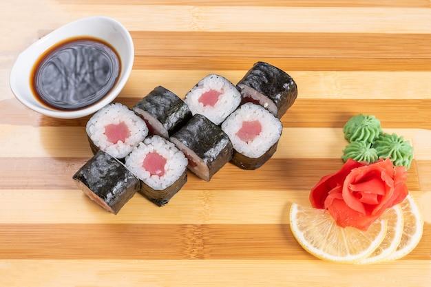 Sushi, roladki z tuńczyka, na desce. na czerwonym tle. w dowolnym celu.