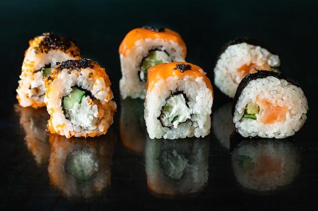 Sushi rolki łosoś, warzywa, imbir, ryż wasabi i nori na stole