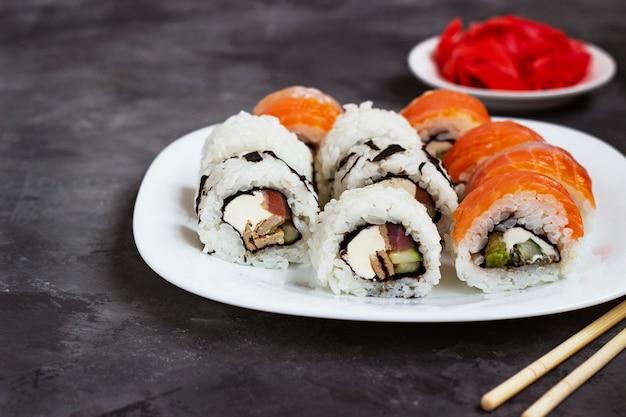 Sushi rolki na białym talerzu na czarnym stole z marynowanym imbirem.