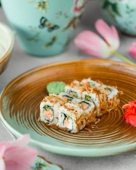 Sushi rolki wewnątrz brązowego talerza.