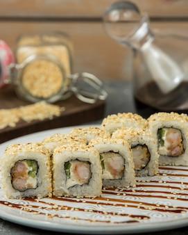 Sushi rolki z białym ryżem i nori w białym talerzu.