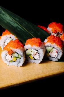 Sushi rolki z czerwonym kawiorem i zielonym liściem na drewnianej desce.