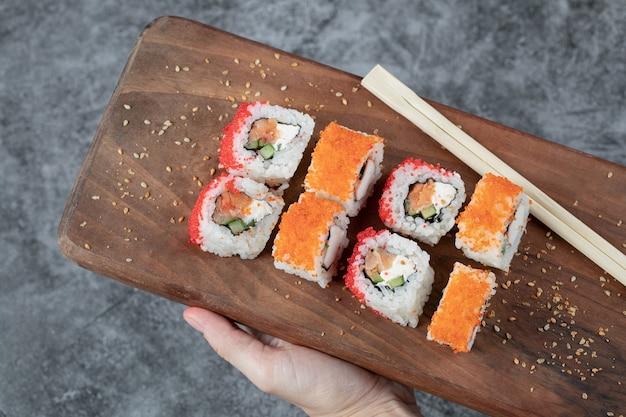 Sushi rolki z żółtym i czerwonym kawiorem na drewnianej desce.