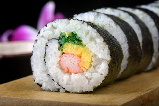 Sushi roll lub japońskie maki z wodorostami jajka i kani pokrojone i ustawione na drewnianym talerzu.