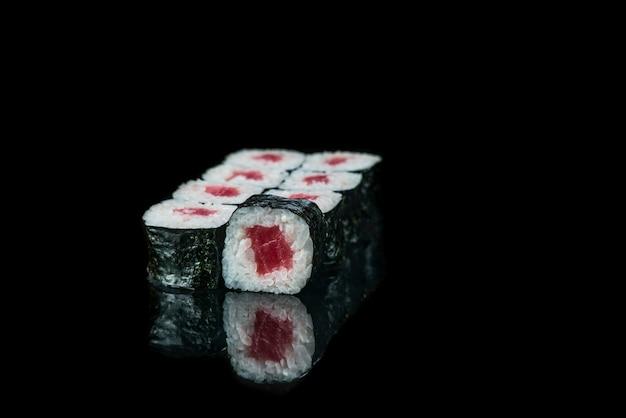 Sushi roll na czarnym tle refleksji japońskie jedzenie bliska