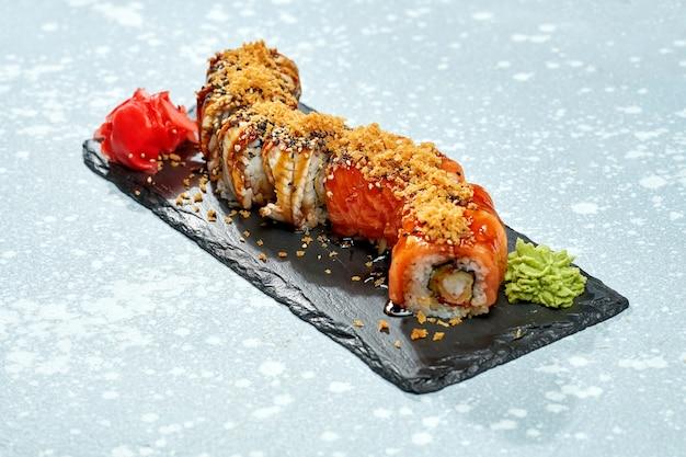 Sushi roll philadelphia z łososiem, krewetkami i węgorzem na czarnym talerzu na jasnym tle