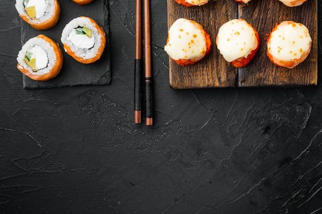 Sushi roll, philadelphia z łososiem, wędzonym węgorzem, awokado, serkiem śmietankowym, na czarnym kamiennym stole, płaski widok z góry