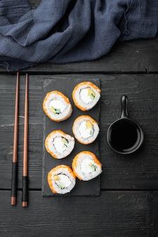 Sushi roll, philadelphia z łososiem, wędzonym węgorzem, awokado, zestawem serków śmietankowych, na czarnym drewnianym stole