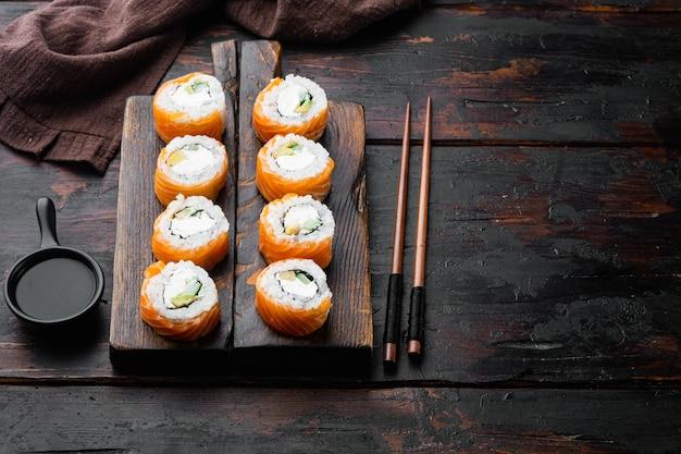 Sushi roll, philadelphia z łososiem, wędzonym węgorzem, awokado, zestawem twarożek, na starym ciemnym drewnianym stole