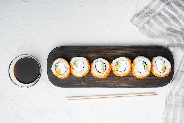 Sushi roll wiersz łososia i tuńczyka z zestawem pałeczki, na białym kamieniu