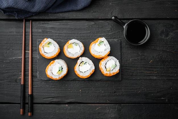 Sushi roll wiersz łososia i tuńczyka z zestawem pałeczki, na czarnym drewnianym stole