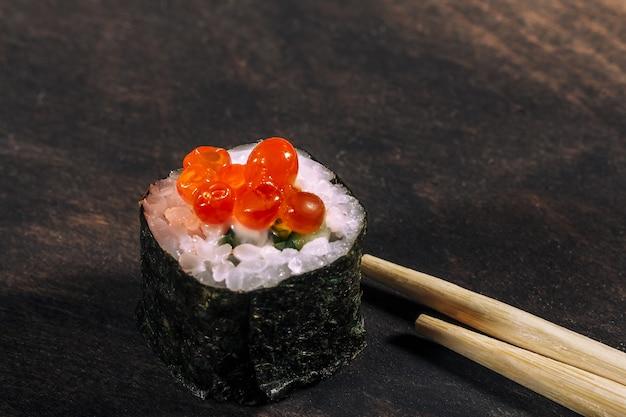 Sushi roll z czerwonym kawiorem na ciemnym drewnianym tle, jedzenie sushi roll w restauracji, selektywne focus. ścieśniać.