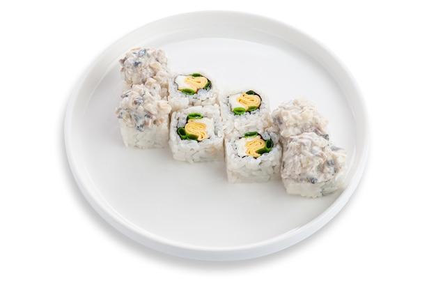 Sushi roll z jajecznicą, zieloną cebulką. świeży ser i małże. na białym talerzu ceramicznym. białe tło. odosobniony.