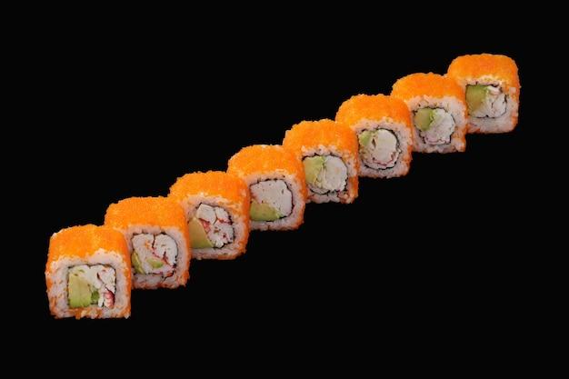 Sushi roll z krabem śnieżnym, awokado, kawiorem masago, majonezem japońskim na czarnym tle
